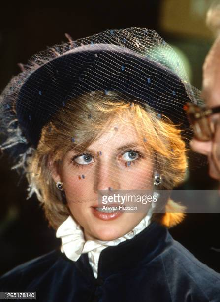 Diana, Princess of Wales, wearing a blue velvet suit with a mandarin collar designed by Caroline Charles and a veiled hat by John Boyd, visits the...