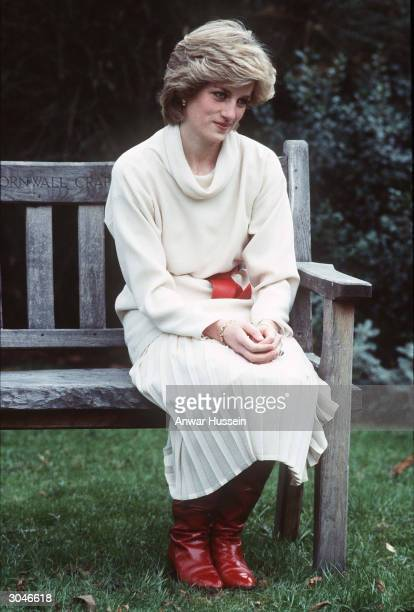Diana, Princess of Wales, wearing a cream cowl neck jumper and pleated skirt with a red belt and boots, sits on a wooden bench that was a wedding...