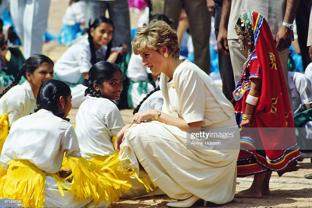 Princess Diana the Princess of Wales bends down to chat with Indian dancers who welcomed her on her arrival in Hyderabad, India in February of 1992.