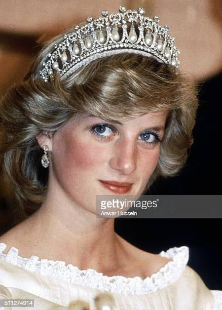 Diana, Princess of Wales, wearing a cream satin dress by Gina Fratini with the Queen Mary Cambridge Lover's Knot Tiara and diamond earrings attends a...