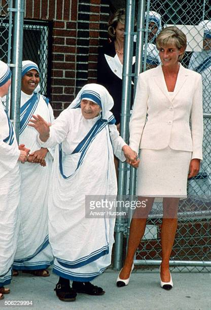 Diana, Princess of Wales, wearing a cream suit, holds hands with Mother Teresa following a meeting in the Bronx on June 18, 1997 in New York, NYC.