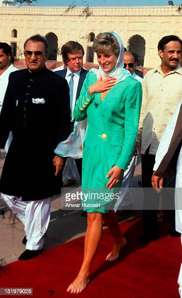 Diana, Princess of Wales, wearing a green dress designed by Catherine Walker, walks with bare feet and covers her head with a headscarf during a...