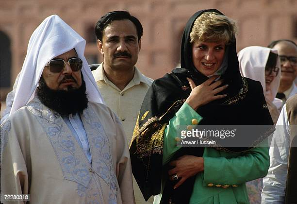 Diana, Princess of Wales, wearing a green dress designed by Catherine Walker, covers her head with a headscarf as she visits the Badshahi Mosque on...