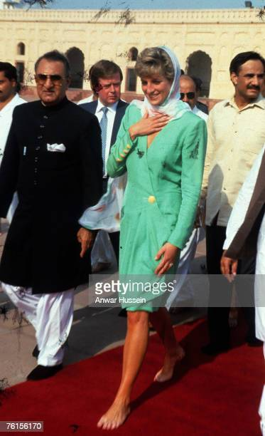 Diana, Princess of Wales, wearing a green dress designed by Catherine Walker, walks with bare feet and covers her head with a headscarf as she visits...