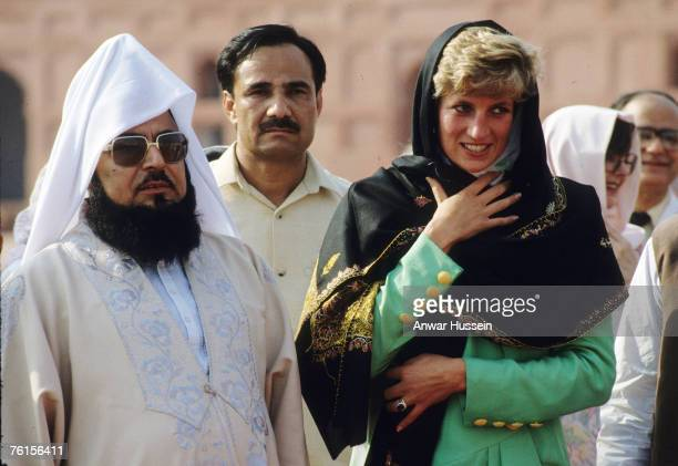 Diana Princess of Wales wearing a green dress designed by Catherine Walker covers her head with a headscarf as she visits the Badshahi Mosque on...