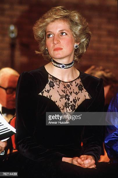 Diana, Princess of Wales, wearing a midnight blue velvet and lace evening gown designed by Catherine Walker and diamond and sapphire velvet choker,...