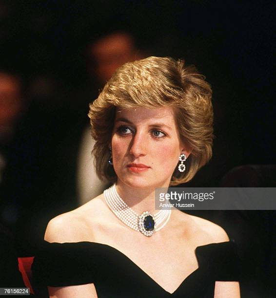 Diana, Princess of Wales, wearing a midnight blue velvet, off the shoulder evening dress designed by Victor Edelstein, a sapphire, diamond and peal...