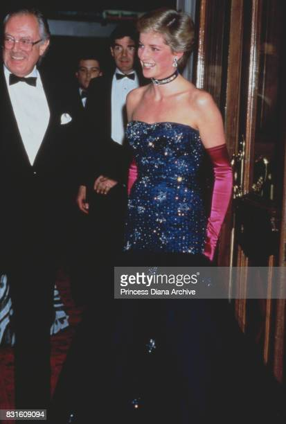 Diana, Princess of Wales wearing a navy blue Murray Arbeid dress and shocking pink long gloves, attends theatre gala of 'Phantom of the Opera',...