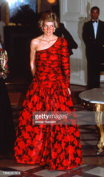 Diana, Princess of Wales, wearing a one-shouldered black and red evening gown designed by Catherine Walker, attends a dinner hosted by the British...
