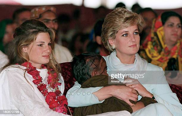 Diana, Princess of Wales, wearing a pale blue shalwar kameez, cradles a young Cancer patient in her arms, as she sits next to Jemima Khan during a...