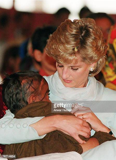 Diana, Princess of Wales, wearing a pale blue shalwar kameez, cradles a young Cancer patient in her arms during a visit to Shaukat Khanum Hospital on...