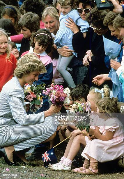 Princess Diana Princess of Wales bends to receive flowers from young children during a walkabout on November 03 1985 in Macedon Australia