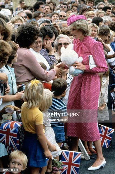 Diana, Princess of Wales, wearing a pink and white polka dot dress designed by Donald Campbell and a pink hat designed by John Boyd, is given a...