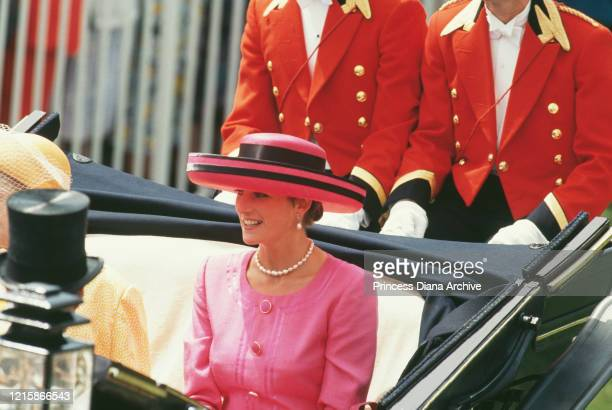 Diana Princess of Wales wearing a pink outfit with a widebrim pink hat with black trim during a Royal Ascot carriage procession at Ascot racecourse...