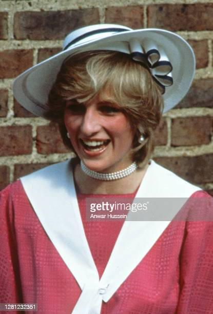 Diana, Princess of Wales, wearing a pink sailor style dress with a white collar and a white hat, attends the wedding of her former flatmate Carolyn...