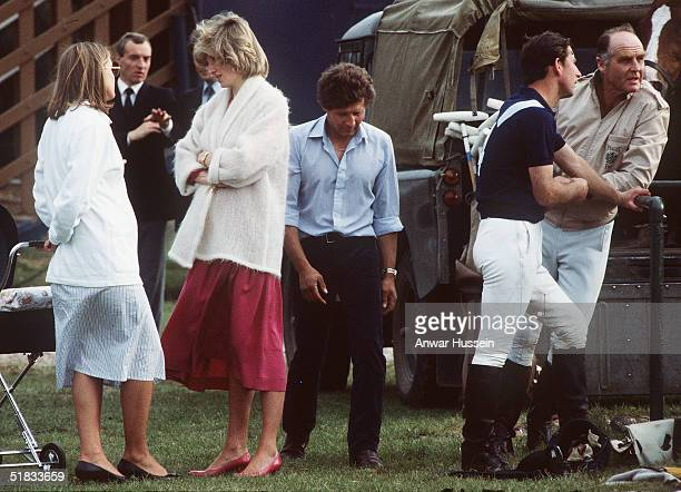 Diana the Princess of Wales pregnant with Prince Harry chats while at a polo event with Prince Charles as bodyguard Barry Mannakee looks on in June...
