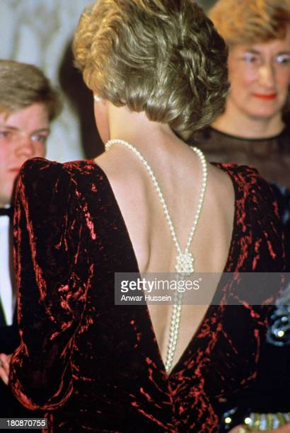 Diana Princess of Wales wearing a plum crushed velvet gown with a low back and pearls attends the film premiere of 'Back to the Future' at the Empire...