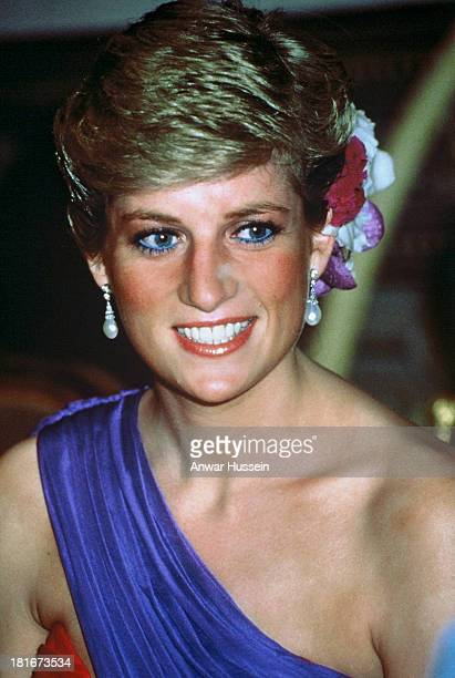 Diana, Princess of Wales, wearing a red and purple chiffon evening dress designed by Catherine Walker with silk flowers in her hair, attends a dinner...