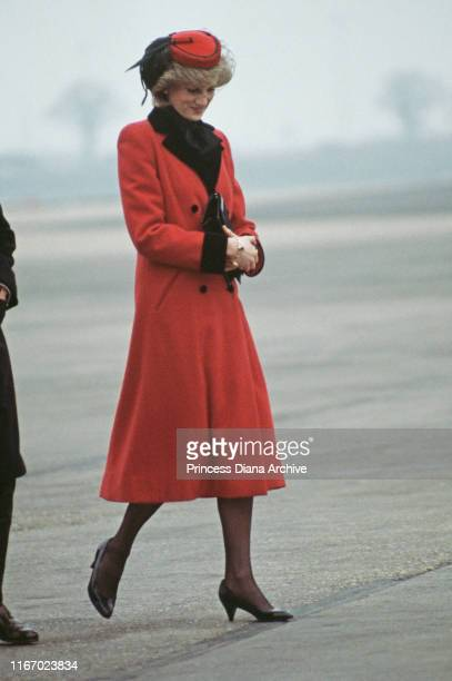 Diana, Princess of Wales wearing a red Catherine Walker coat and a hat by John Boyd upon her arrival at Birmingham airport, England, February 1984.