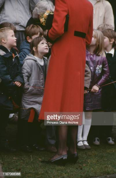 Diana, Princess of Wales wearing a red coat by Catherine Walker and black tights with a red seam at the back, during a visit to the Royal School for...
