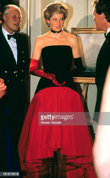 Diana Princess of Wales wearing a Murray Arbeid flamenco dress with one red glove and one back glove attends the America's Cup Ball at the Grosvenor...