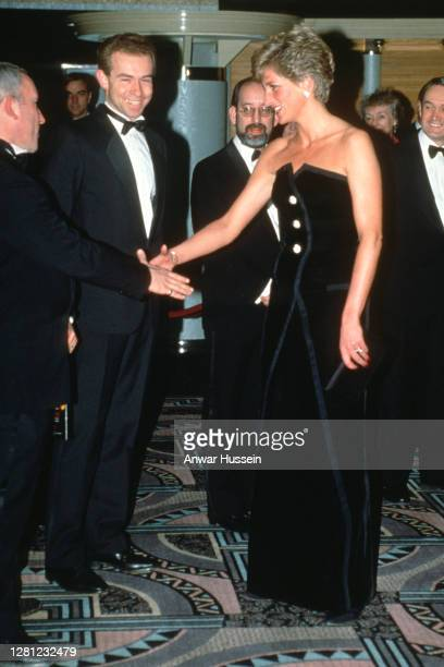 Diana, Princess of Wales, wearing a strapless, black velvet dress with gold buttons designed by Victor Edelstein, attends the film premiere of...