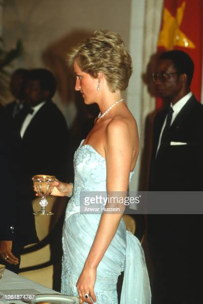 Diana, Princess of Wales, wearing a strapless blue chiffon and lace dress with sequins designed by Catherine Walker and diamond and pearl earrings...