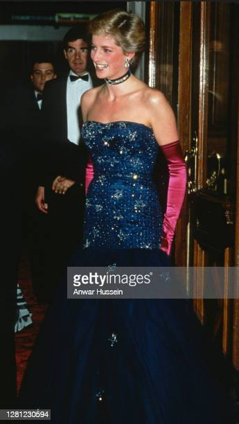 Diana, Princess of Wales, wearing a strapless blue dress designed by Murray Arbeid and long, pink gloves, attends the premiere of Andrew Lloyd...
