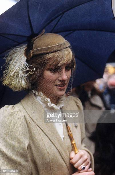 Princess Diana Princess of Wales wearing a Caroline Charles beige coat and a John Boyd hat shelters from the rain under an umbrella during a visit to...