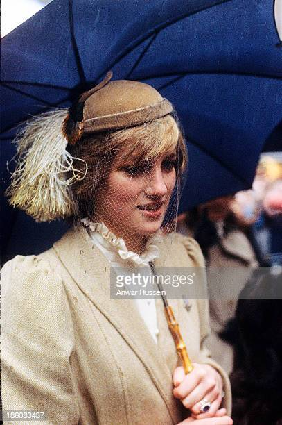 Princess Diana Princess of Wales wearing a John Boyd hat shelters from the rain under an umbrella during her first official visit to Wales on...