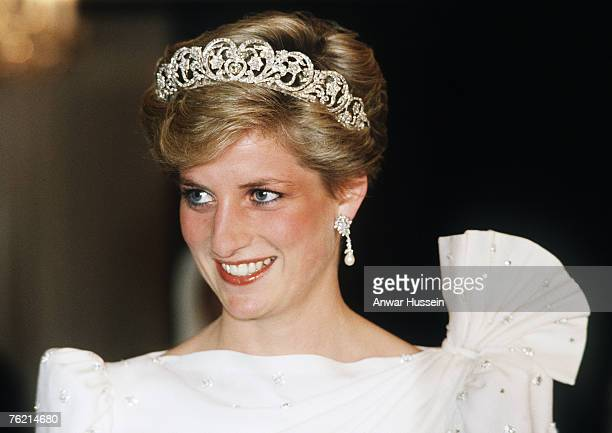 Diana, Princess of Wales, wearing a white dress designed by David and Elizabeth Emanuel with the Spencer Tiara, attends a State Banquet on November...