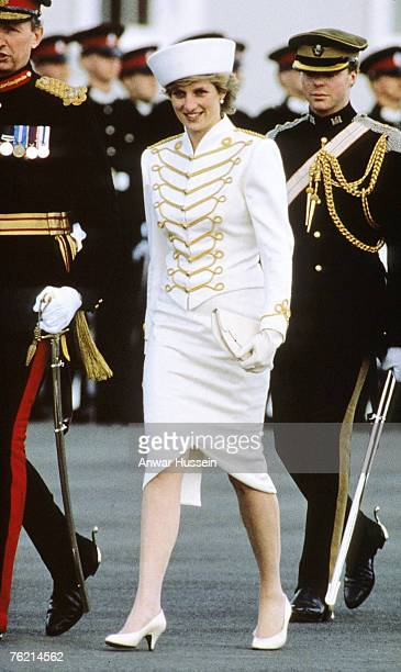 Diana, Princess of Wales, wearing a white military suit with gold majorette drum frogging and epaulettes designed by Catherine Walker and a white hat...