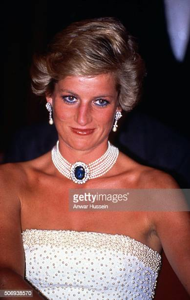 Princess Diana, Princess of Wales wearing a white strapless dress, embroidered with pearls, designed by Catherine Walker and a pearl and sapphire...