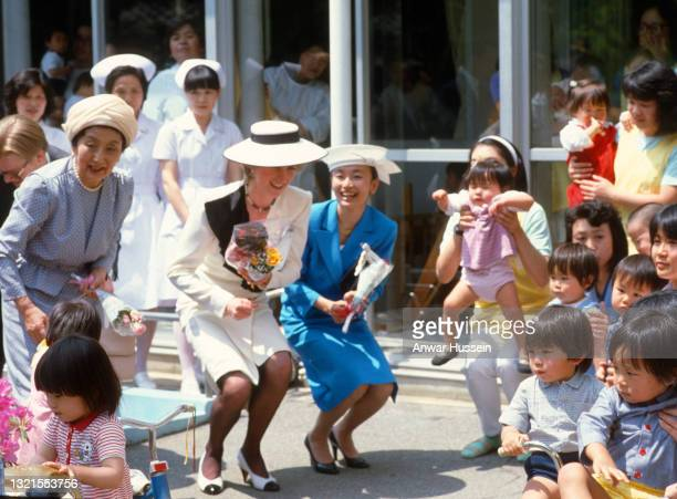 Diana, Princess of Wales, wearing a white suit with a half black collar and a white hat, visits the Red Cross Infants' Home on May 13, 1986 in Tokyo,...