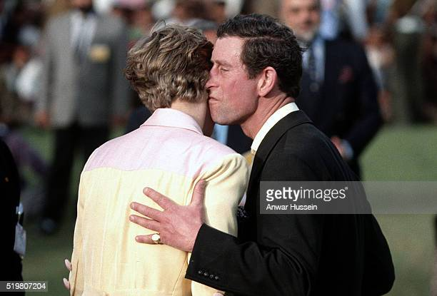 Diana, Princess of Wales, wearing a yellow and pink suit designed by Catherine Walker, and Prince Charles, Prince of Wales kiss during a prize giving...
