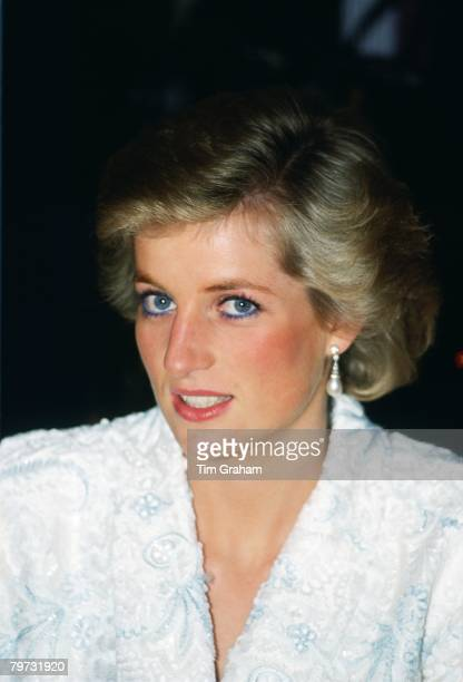 Diana, Princess of Wales wears a white and blue lace and sequin evening coat-dress designed by Catherine Walker for a dinner at the Chateau de...