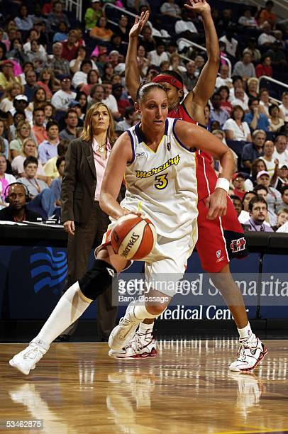 Diana Taurasi of the Phoenix Mercury drives against Dominique Canty of the Houston Comets in WNBA action August 25 2005 at America West Arena in...