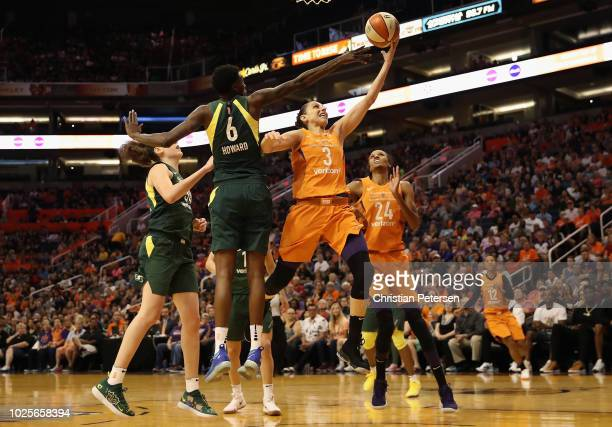 Diana Taurasi of the Phoenix Mercury lays up a shot past Natasha Howard of the Seattle Storm during game three of the WNBA Western Conference Finals...