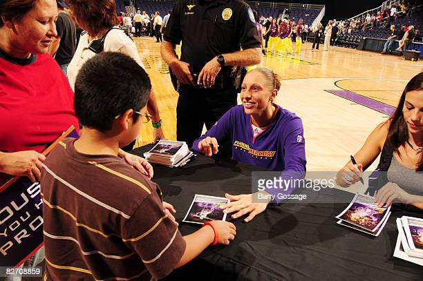 Diana Taurasi of the Phoenix Mercury signs autographs for fans following the game against the Houston Comets on September 7 at US Airways Center in...