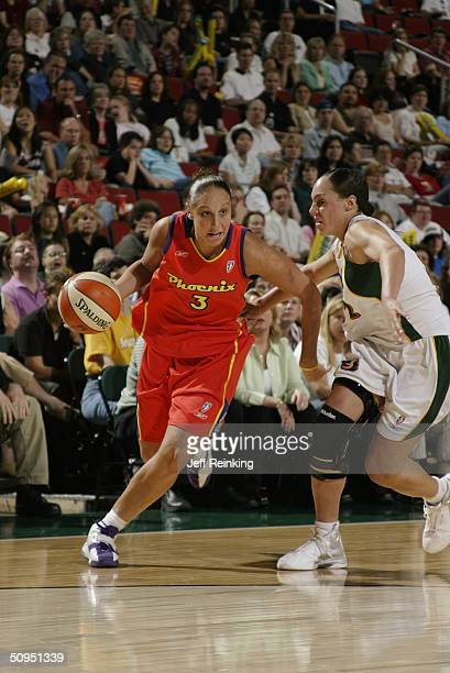 Diana Taurasi of the Seattle Storm drives around Adia Barnes of the Phoenix Mercury during the game at Key Arena on June 3 2004 in Seattle Washington...