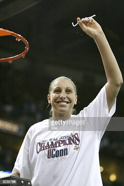 Diana Taurasi of the University of Connecticut Huskies cuts down the net and waves to the crowd after defeating the Tennessee Lady Vols 7061 in the...