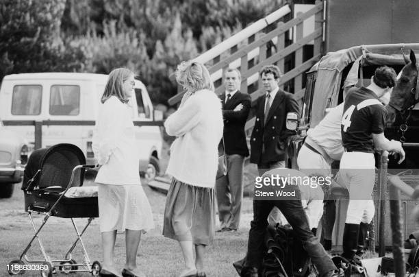 Diana the Princess of Wales pregnant with Prince Harry chats while at a polo event with Prince Charles as bodyguard Barry Mannakee looks on Windsor...