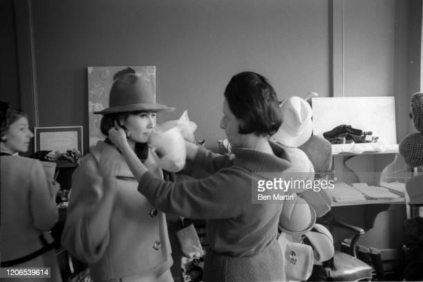 Diana Vreeland Fashion Editor of Harper's Bazaar adjusting a model's hat May 1 1953