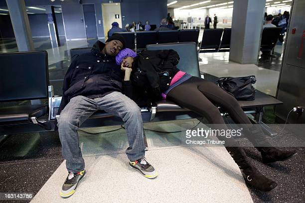 Diandre Hines and Shauntae McKnight both of Chicago sleep while charging their phone at O'Hare International Airport Tuesday March 5 2013 as a...