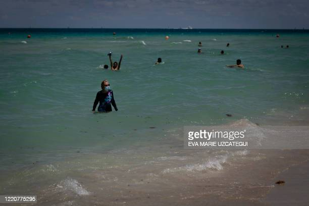 Diane, a nurse from Houston, Texas, bathes at the beach wearing a facemask, in Miami Beach, Florida on June 16, 2020. - Florida is reporting record...