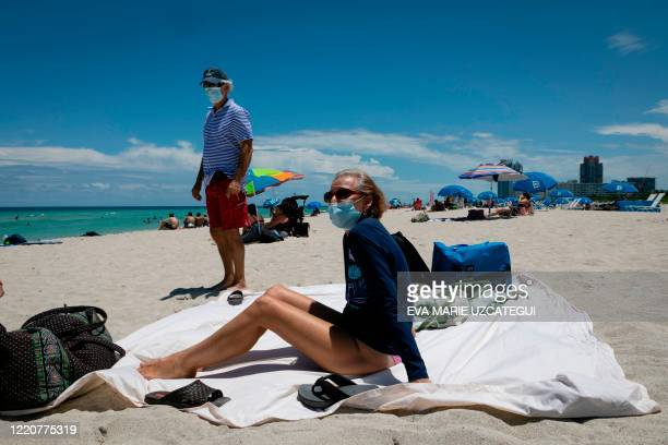 Diane a nurse from Houston Texas sunbathes at the beach next to her husband both wearing facemasks in Miami Beach Florida on June 16 2020 Florida is...