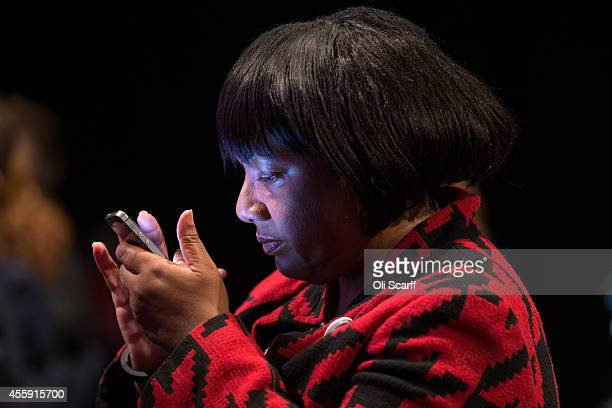 Diane Abbot MP uses her mobile phone in the main hall of the Labour Party Conference on September 22 2014 in Manchester England The fourday annual...