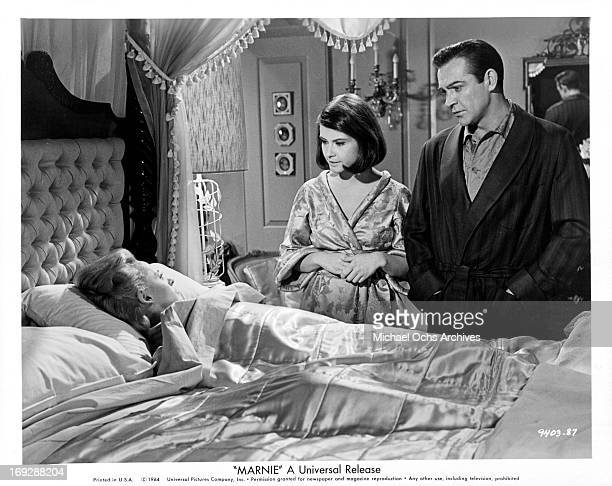 Diane Baker and Sean Connery come to the bedside of Tippi Hedren in a scene from the film 'Marnie' 1964