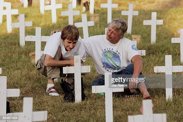 Diane Baker from Dallas Texas and Bob Oehmen from Chicago Illinois spend a moment together among crosses setup to represent soldiers who have died in...