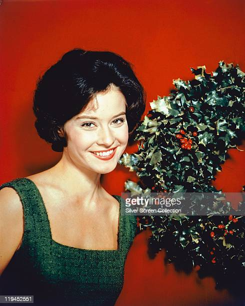 Diane Baker US actress wearing a green dress and standing beside a Christmas wreath in a studio portrait against a red background circa 1960